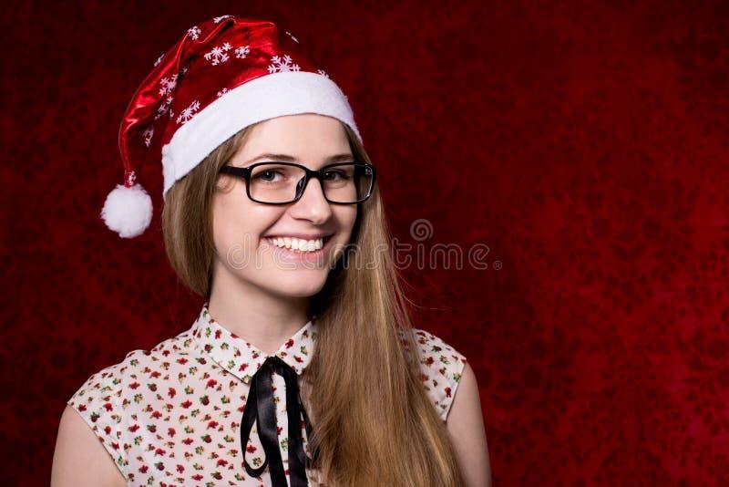 Красивая усмехаясь девушка с стеклами в шляпах Санты смотря стоковые изображения