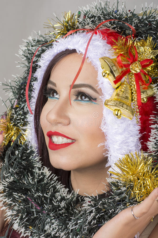 Красивая усмехаясь египетская женщина в костюме Санта Клауса смотря дерево круга рождества хода стоковые изображения rf