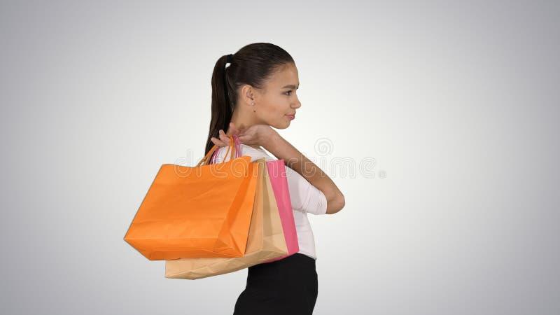 Красивая усмехаясь женщина в официальном платье идя с красочными хозяйственными сумками на предпосылке градиента стоковая фотография