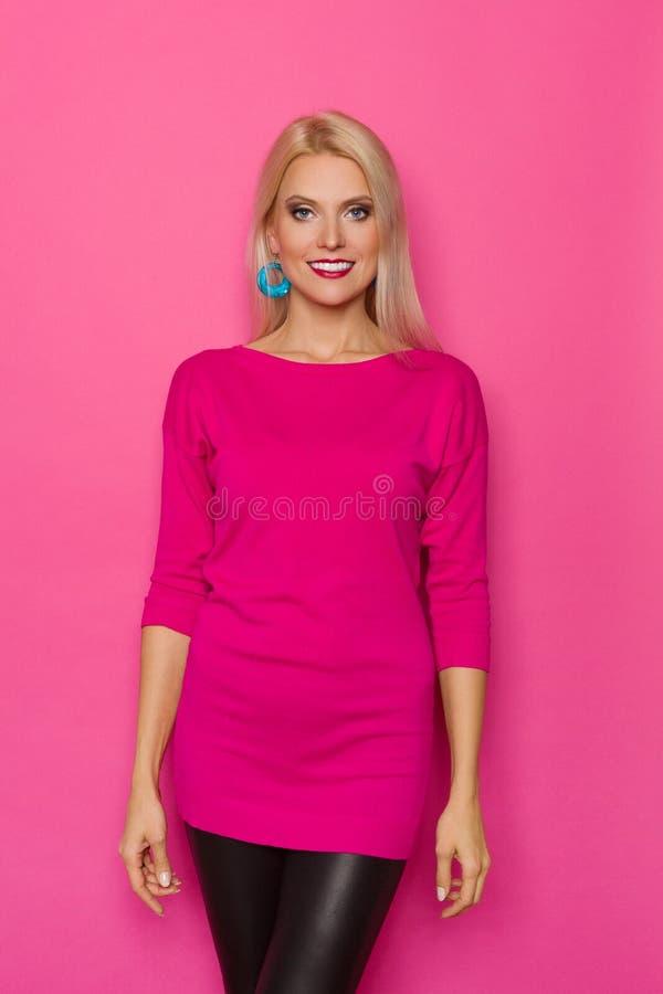 Красивая усмехаясь женщина в розовом свитере стоковое фото rf
