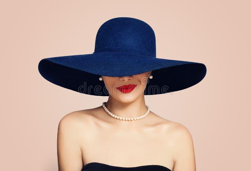 Красивая усмехаясь женщина в элегантной шляпе на розовой предпосылке Стильная девушка с красным макияжем губ, портрет моды стоковая фотография rf