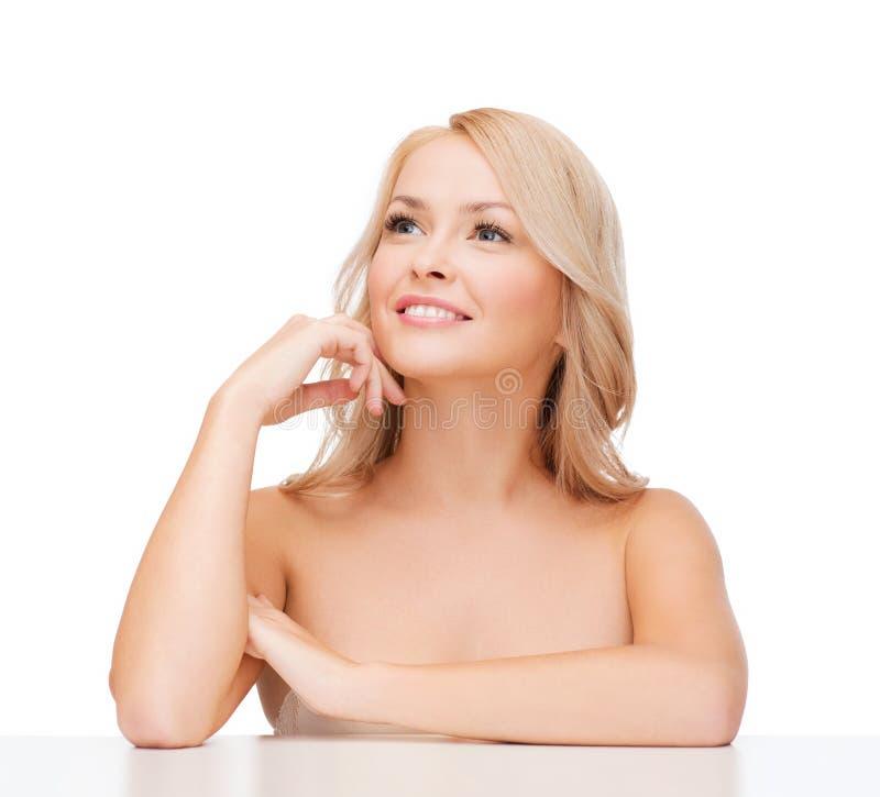 Красивая усмехаясь женщина касаясь ее стороне стоковая фотография