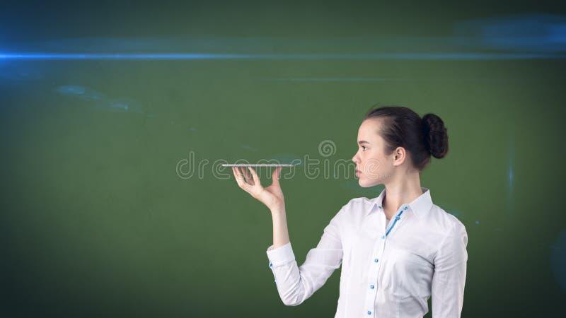 Красивая усмехаясь женщина поворачивая головной и держа поднос, смотря что-то Изолированная предпосылка студии с copyspace стоковое изображение