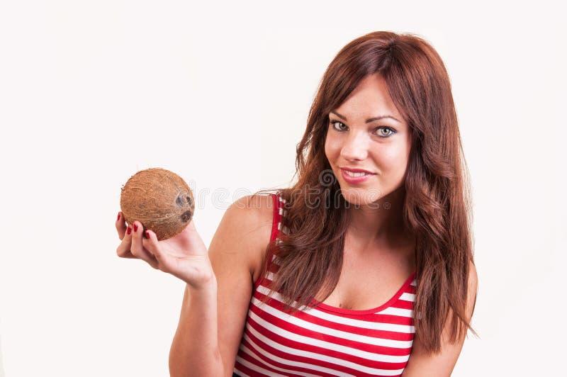 Красивая усмехаясь женщина показывает кокос, космос экземпляра стоковое изображение rf