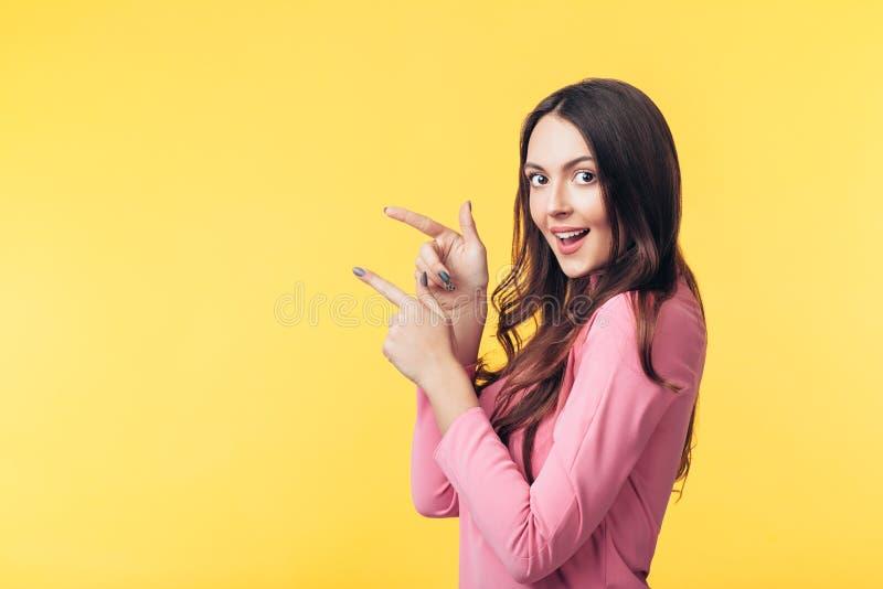 Красивая усмехаясь женщина показывая пустой космос экземпляра указывая ее пальцы изолированные на желтой предпосылке стоковое фото rf