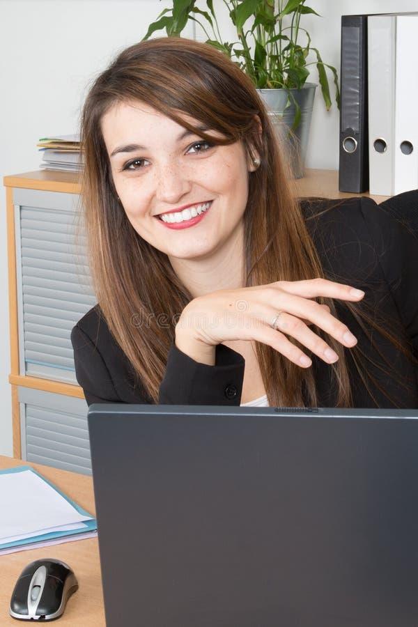 красивая усмехаясь женщина работая в офисе на компьтер-книжке стоковые фотографии rf