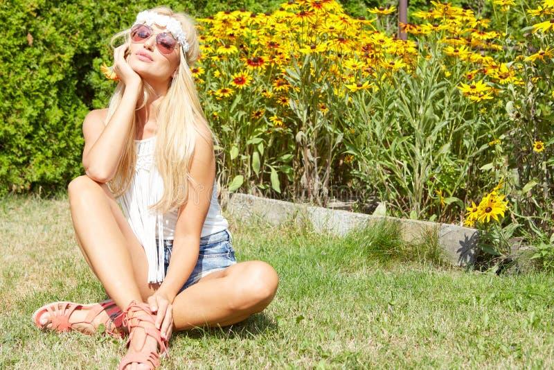 Красивая усмехаясь женщина сидя на траве внешней стоковая фотография