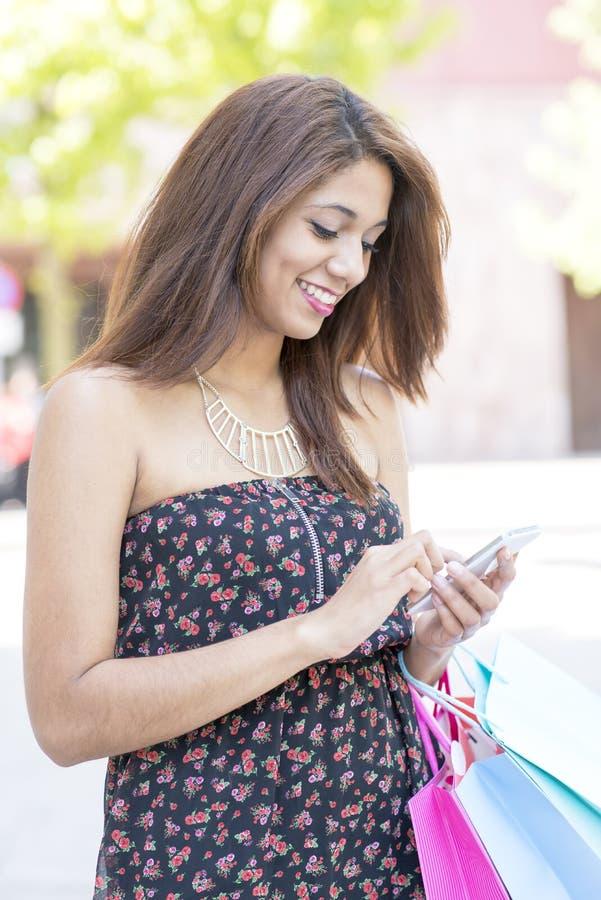 Красивая усмехаясь женщина смотря и пишет сообщение на умном телефоне стоковые фотографии rf