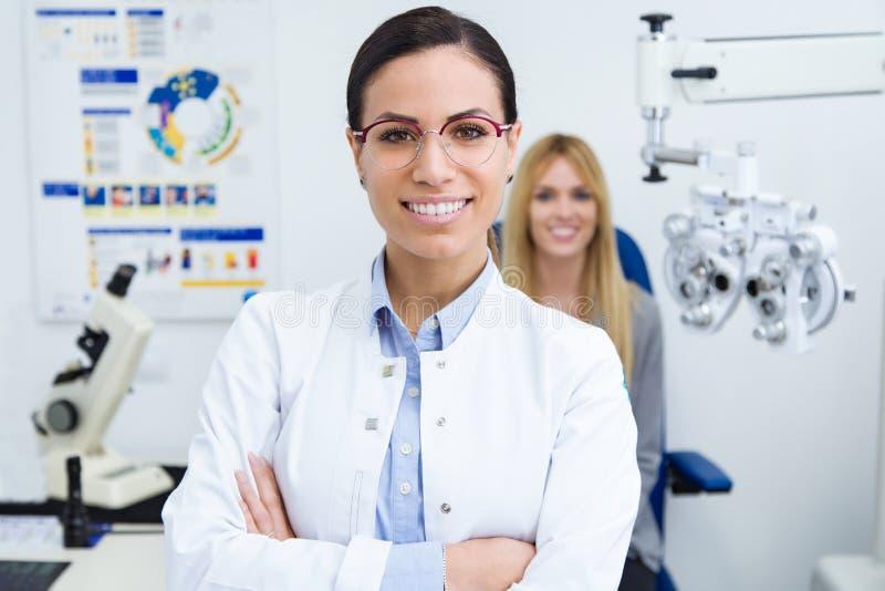 Красивая усмехаясь женщина смотря камеру в клинике офтальмологии с пациентом женщины сидя для теста глаза в предпосылке стоковая фотография