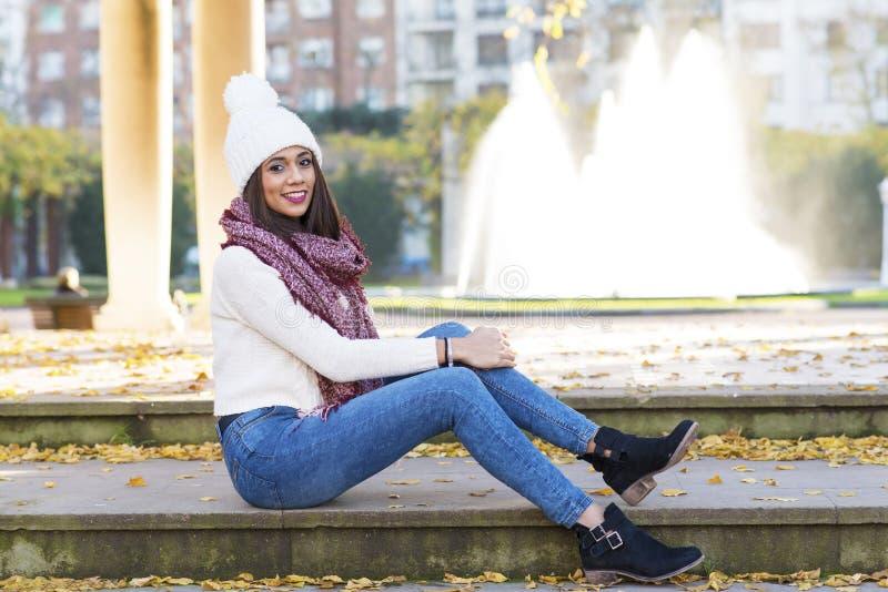 Красивая усмехаясь женщина с и крышка шарфа сидя на лестницах вне стоковое изображение rf