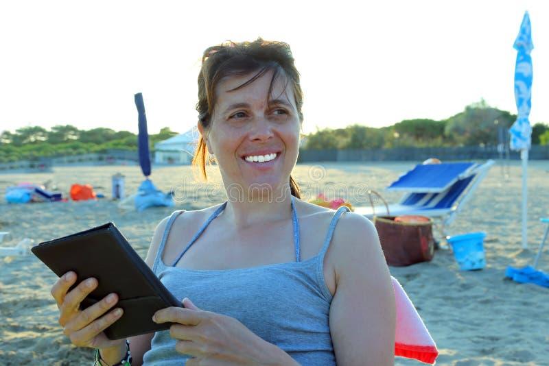 Красивая усмехаясь женщина читает ebook на пляже стоковое изображение rf