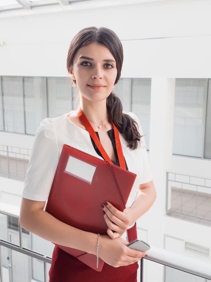 Красивая усмехаясь коммерсантка стоя против белой предпосылки офисов Портрет бизнес-леди с папкой в ее руках стоковое изображение