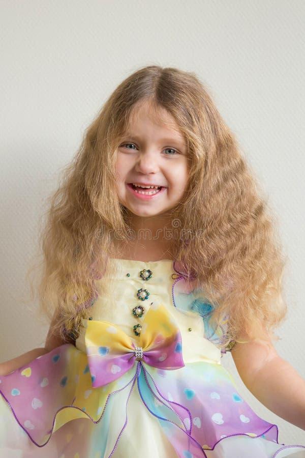 Красивая усмехаясь маленькая девочка с длинным белокурым вьющиеся волосы стоковое фото rf