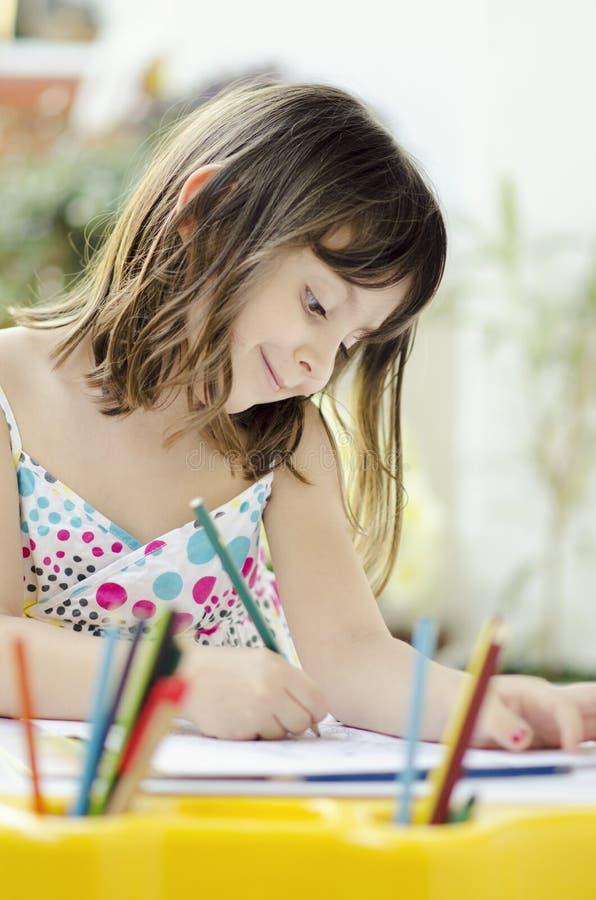 Красивая усмехаясь маленькая девочка рисуя дома стоковые фото