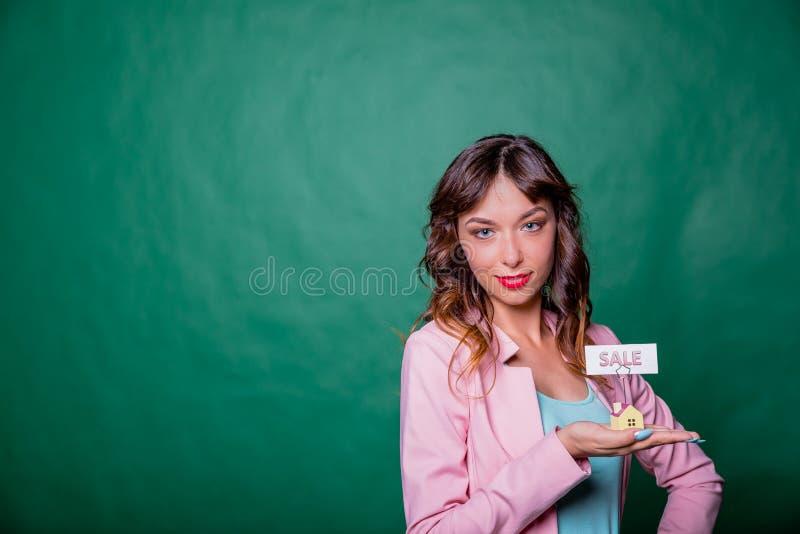 Красивая усмехаясь молодая женщина в розовом jaket при длинные волосы, держа малый деревянный дом в ее руках с сообщением для стоковые изображения rf