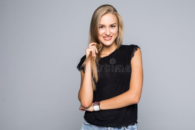 Красивая усмехаясь молодая женщина изолированная на серой предпосылке стоковые фото
