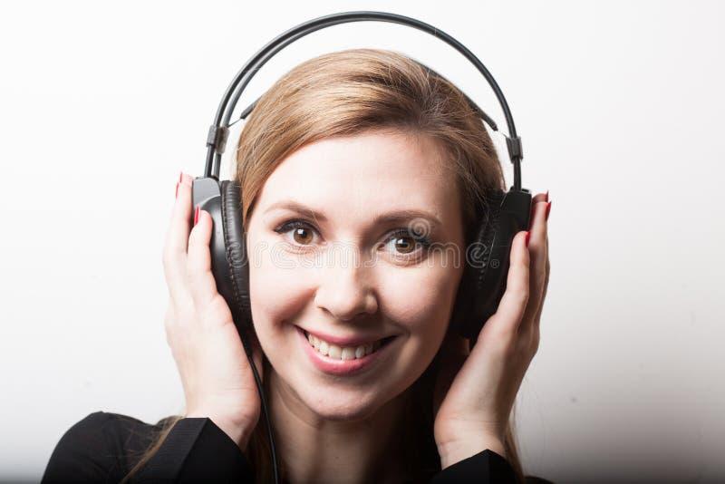 Красивая усмехаясь музыка женщины слушая в наушниках стоковое изображение rf