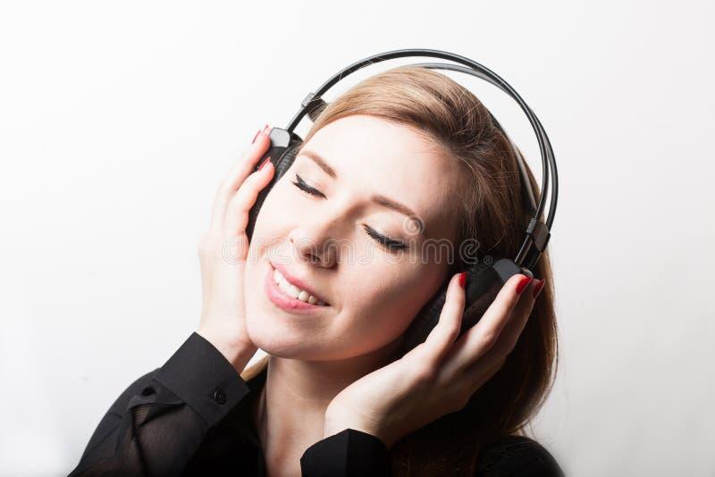 Красивая усмехаясь музыка женщины слушая в наушниках стоковые изображения