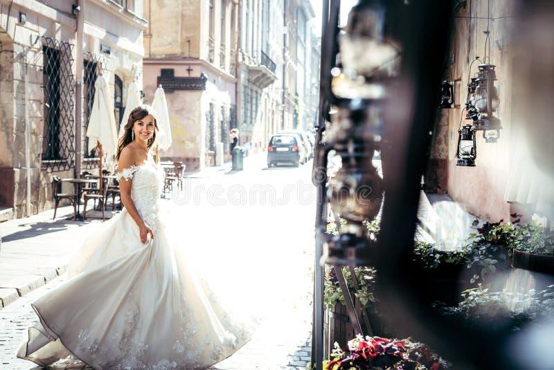 Красивая усмехаясь невеста в стильном длинном платье свадьбы закручивая в солнечную улицу стоковая фотография