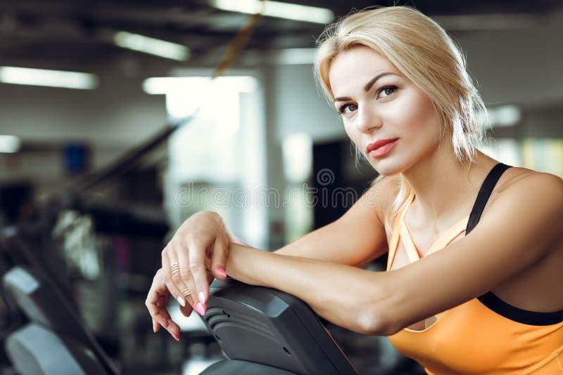 Красивая утомленная белокурая женщина на третбане в спортзале после разминки стоковые изображения rf