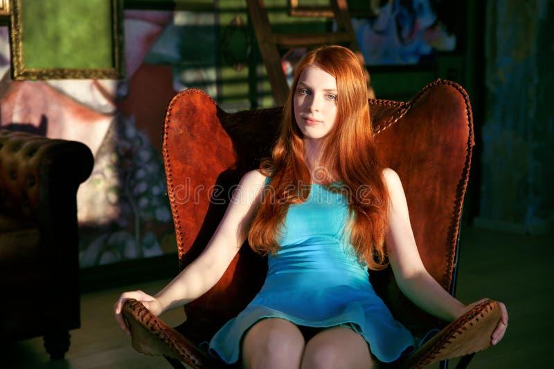 Красивая уточненная девушка с длинными красными волосами в голубой сидеть платья ослабила в кожаном коричневом стуле стоковое изображение rf