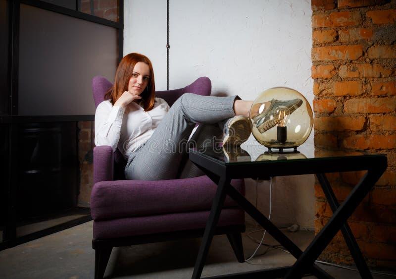 Красивая уточненная девушка с длинным красным усаживанием волос ослабленным в кожаном коричневом стуле Яркие теплые цвета, образ  стоковое фото