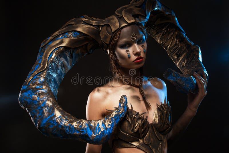 Красивая худенькая девушка в костюме с рожками на хеллоуин на черной предпосылке стоковые изображения rf