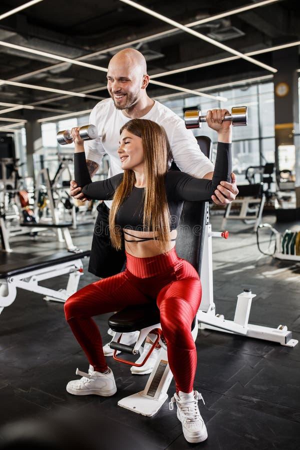 Красивая худенькая девушка в стильных одеждах спорт делает жим лежа гантели вверх по сидеть на стенде пока атлетическое стоковые фотографии rf
