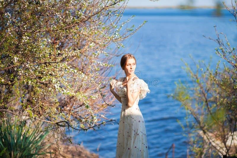 Красивая худенькая девушка с белокурыми волосами в длинном светлом платье против фона природы, цветя деревьев, голубого моря, oce стоковое изображение rf