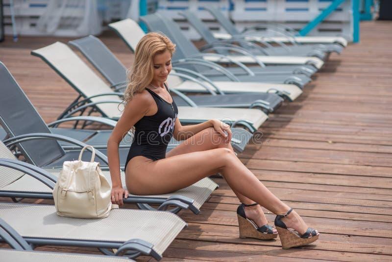 Красивая худенькая девушка в купальнике лежит на deckchair стоковые фотографии rf