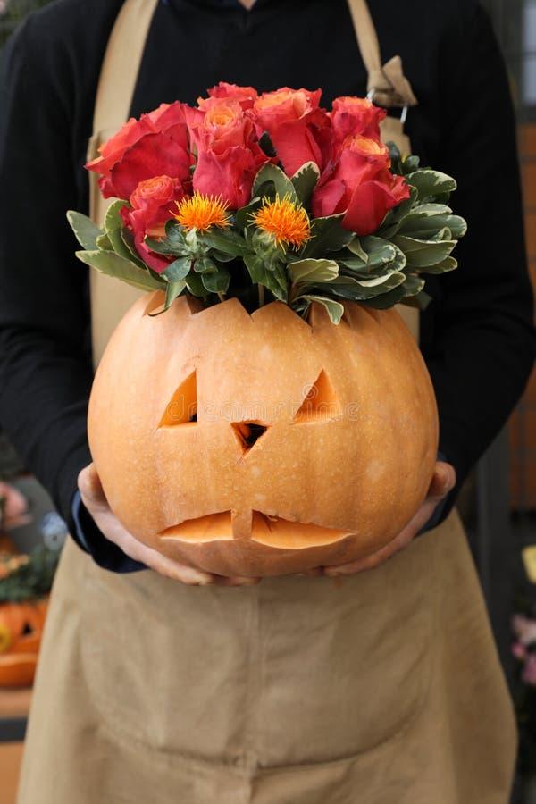 Красивая цветочная композиция красных роз цвета тыквы и томата для торжества хеллоуина в руках флориста стоковое изображение rf