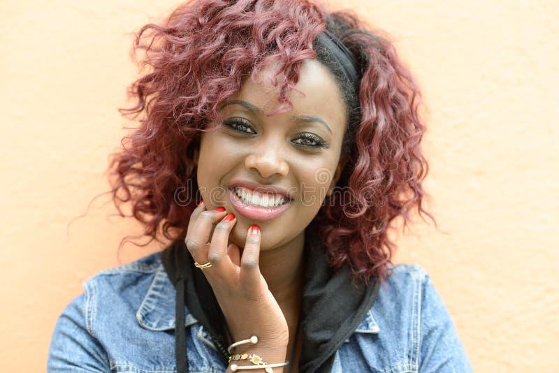 Красивая чернокожая женщина в городской предпосылке с красными волосами стоковое изображение