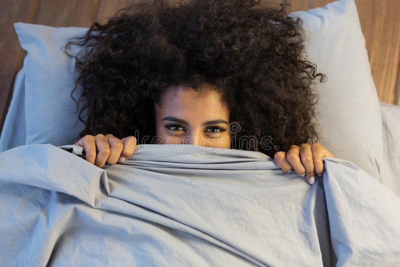 Красивая чернокожая женщина пряча за одеялом и усмехаться стоковые фотографии rf