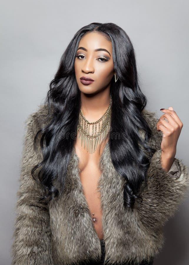 Красивая чернокожая женщина с длинным вьющиеся волосы стоковые изображения