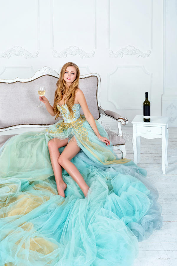 Красивая чувственная белокурая женщина в шикарном длинном платье держа стекло белого вина и бутылки Праздновать маленькой девочки стоковое фото rf