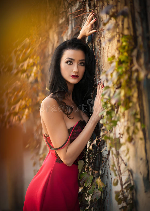 Красивая чувственная женщина в красном платье представляя в осеннем парке Молодая женщина брюнет daydreaming около стены с ржавым стоковое фото rf