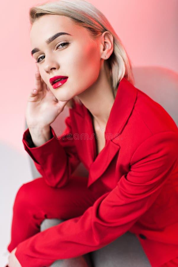 красивая чувственная стильная женщина в красных одеждах представляя в кресле стоковое изображение rf