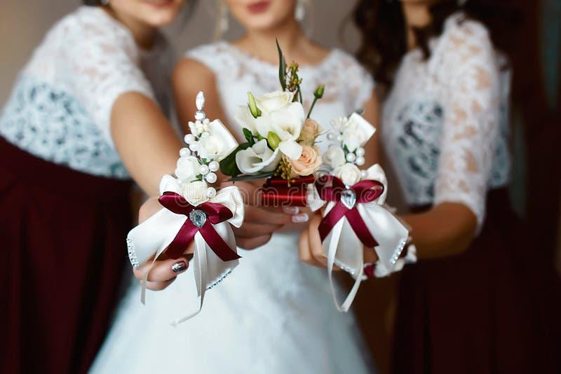 Красивая чувствительная свадьба более boutonier с бургундскими и белыми цветками в руках невесты и девушек стоковая фотография rf