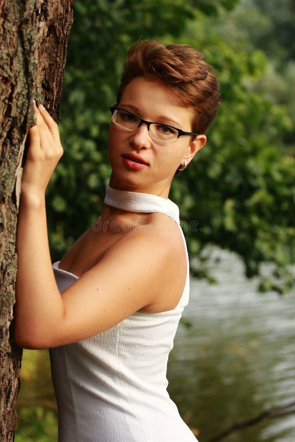 Красивая эмоциональная девушка в белом платье стоя на дереве стоковое изображение