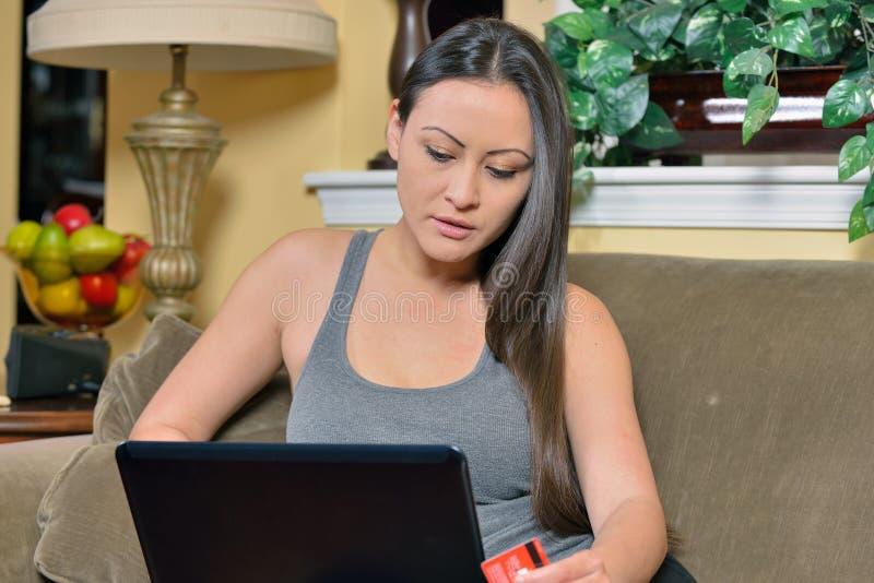 Красивая Biracial женщина используя покупки компьтер-книжки компьютерные стоковое фото