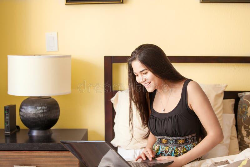 Красивая biracial предназначенная для подростков девушка на кровати смотря компьтер-книжку стоковые фотографии rf