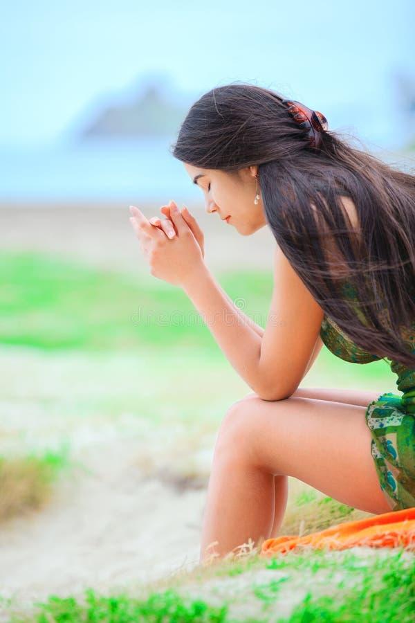 Красивая biracial предназначенная для подростков девушка сидя на тропическом пляже, моля стоковая фотография