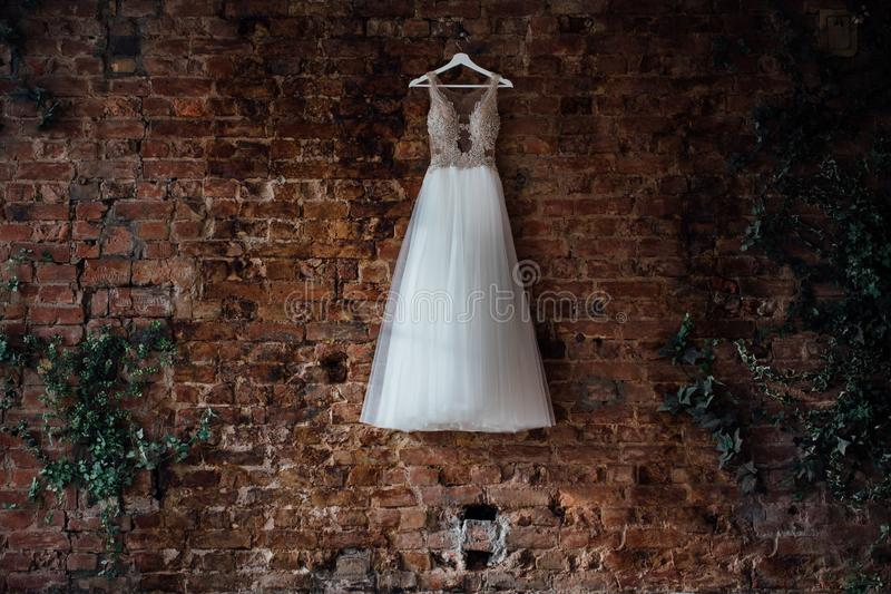 Красивая bridal смертная казнь через повешение платья свадьбы на вешалке на кирпичной стене в студии просторной квартиры Никто стоковые фото