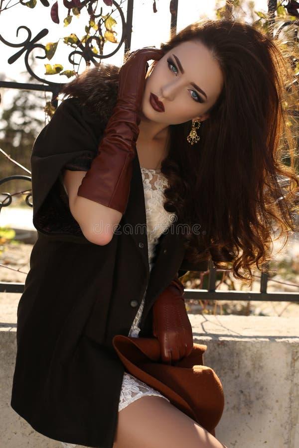 Красивая ladylike женщина с темными волосами в элегантном пальто и кожаных перчатках стоковое изображение