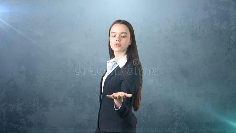 Красивая longhair коммерсантка брюнет показывая что-то незримое перед ей с copyspace стоковая фотография