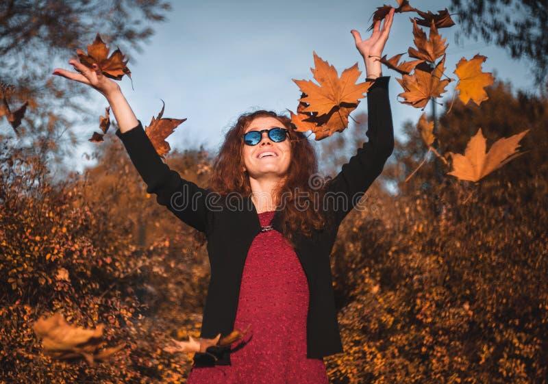 Красивая redhaired девушка с падая листья стоковая фотография