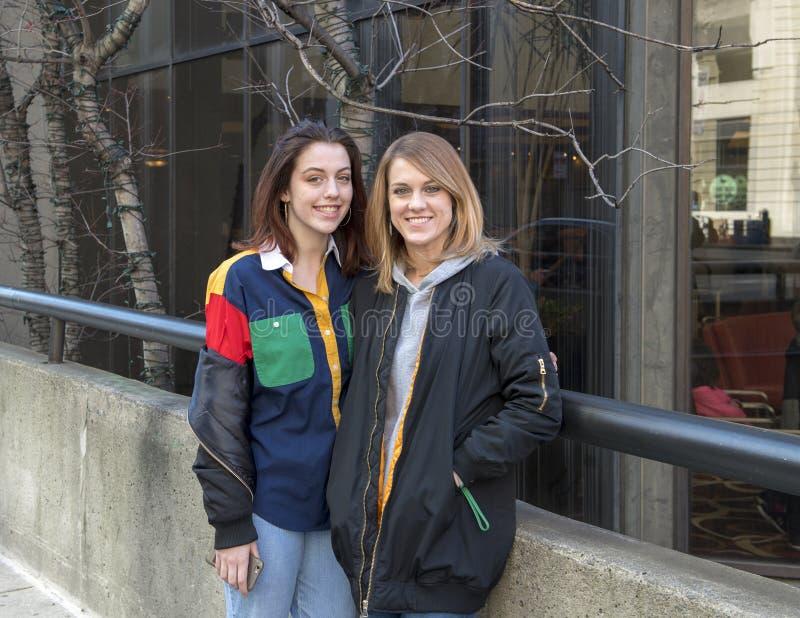 Красивая redheaded женщина и ее дочь-подросток на тротуаре в разбивочном городе, Филадельфии стоковая фотография