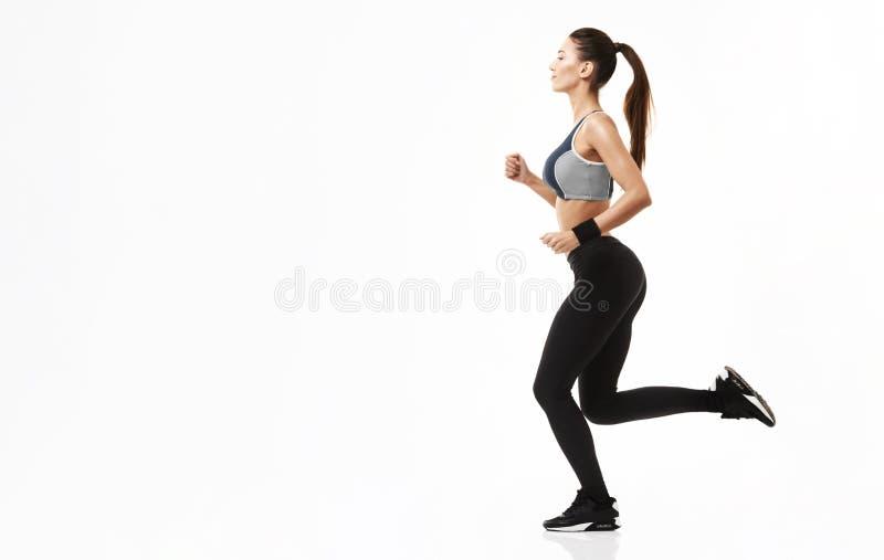 Красивая sportive девушка в тренировке sportswear бежать над белой предпосылкой скопируйте космос стоковое фото rf