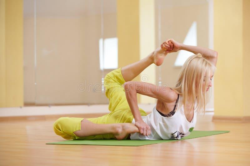 Красивая sporty женщина yogi пригонки практикует asana Gherandasana йоги в тренажерном зале стоковые изображения rf