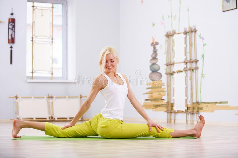 Красивая sporty женщина yogi пригонки практикует asana Hanumanasana йоги - Monkey представление в тренажерный зал стоковые изображения rf